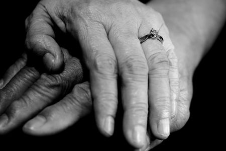 aged: A black and white shot of a senior couple holding hands Stock Photo