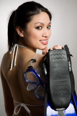 A shot of a beautiful asian woman wearing bikini and carrying snorkeling equipment