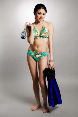 A shot of a beautiful asian woman in swimsuit carrying snorkeling equipment photo