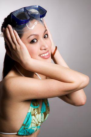 A beautiful asian woman in bikini wearing snorkeling goggles