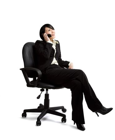secretary phone: An isolated shot of a businesswoman sitting on a chair and talking on the phone
