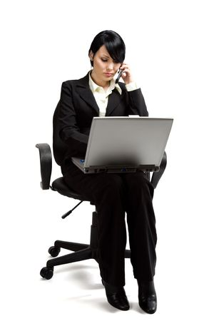 A shot of a businesswoman working on her laptop while talking on the phone photo