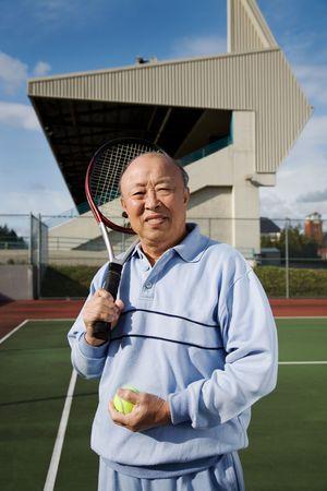 70s tennis: A shot of a senior asian man playing tennis