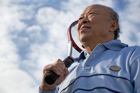 tennis stadium: A shot of a senior asian man holding a tennis racquet