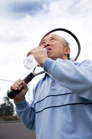 A shot of a senior asian tennis player drinking water while resting photo