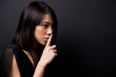 A shot of a beautiful asian woman with hands on her lips shushing Stock Photo