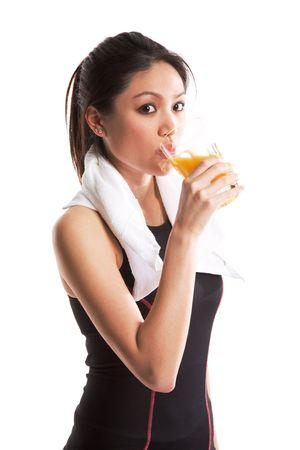 vaso de jugo: Un tiro aislado de una mujer asi�tica sana que bebe un cristal de jugo anaranjado despu�s de ejercitar Foto de archivo