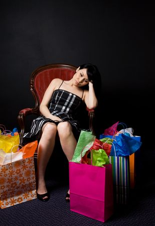 A shot of a tired and exhausted beautiful woman resting on a chair after shopping Stock Photo - 2894289