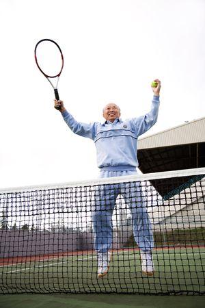 70s tennis: An asian senior tennis player jumping for joy
