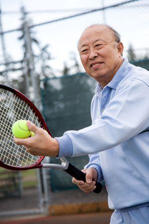 70s tennis: A shot of an senior asian man playing tennis