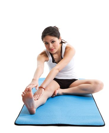 An isolated shot of an asian woman stretching on a yoga mat Stock Photo - 2927536