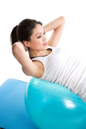 An isolated shot of an asian woman doing sit-up on an exercise ball photo