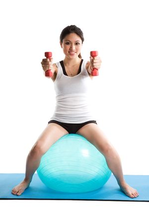 An isolated shot of an asian woman sitting on an exercise ball lifting dumbbells photo
