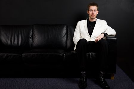 sofa: A portrait of a casual caucasian businessman sitting on a couch