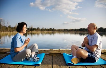 A shot of a senior couple practicing a yoga exercise and meditating outdoor photo