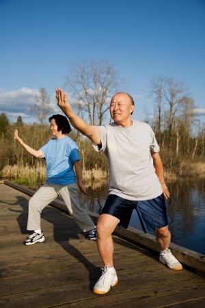 A shot of a senior couple practicing tai-chi exercise photo