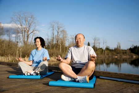 A shot of a senior asian couple practicing yoga and meditating photo