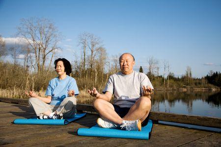 A shot of a senior asian couple practicing yoga and meditating photo