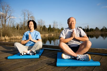 A shot of a senior asian couple meditating and practicing yoga photo