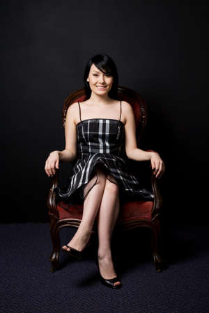 antique chair: A portrait of a beautiful young woman sitting on a retro chair