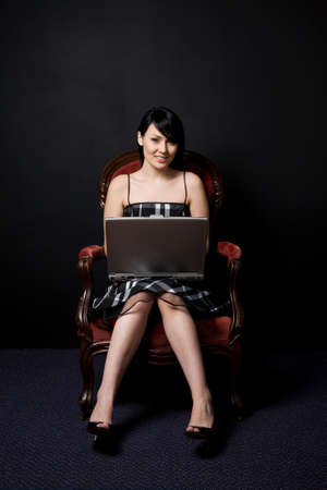 A portrait of a beautiful woman working on her laptop while sitting on a vintage chair photo