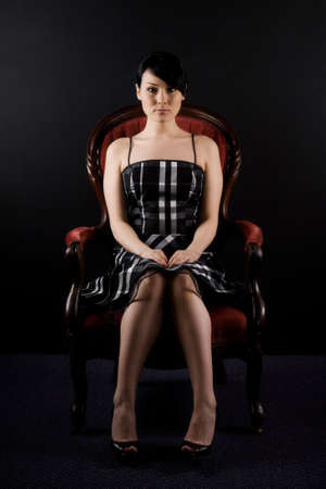 A portrait of a beautiful woman sitting on a vintage chair photo