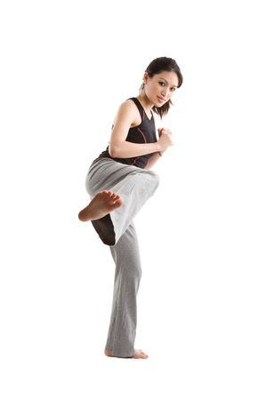 martial arts woman: An isolated shot of happy beautiful asian woman doing a martial arts kicking