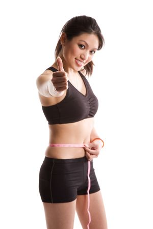 An isolated shot of a healthy asian woman measuring her waistline and giving a thumbs up Stock Photo - 3001623