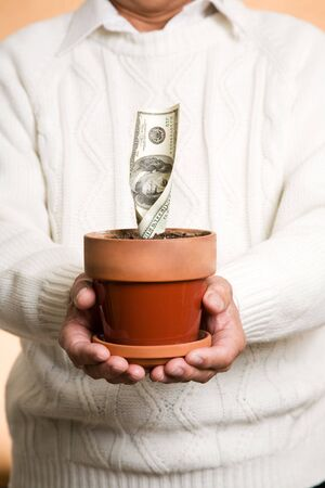 us money: A shot of a businessman holding a pot with money planted, can be used for financial or investment or savings concept