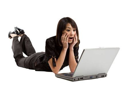 An isolated shot of a surprised asian woman looking at her laptop photo
