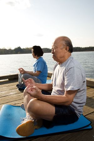 A shot of a senior asian couple meditating and practicing yoga photo