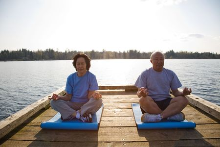 A shot of senior asian couple exercising and practicing yoga photo