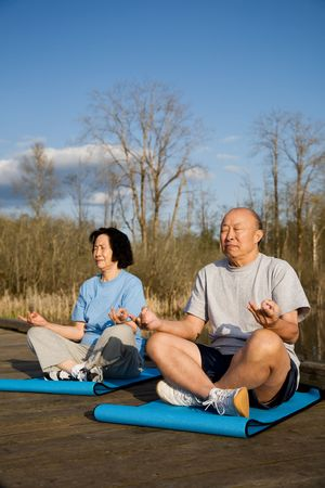 A shot of senior asian couple practicing yoga and meditating photo