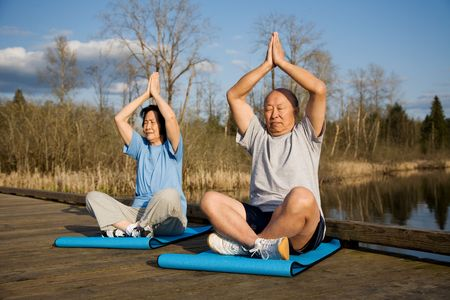 A senior asian couple meditating and practicing yoga photo