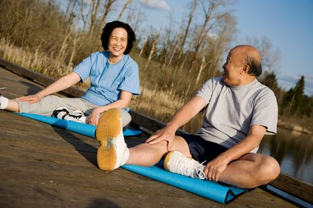 A senior asian couple stretching before exercise photo