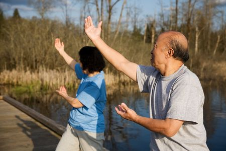 A shot of a senior asian couple doing tai-chi exercise photo