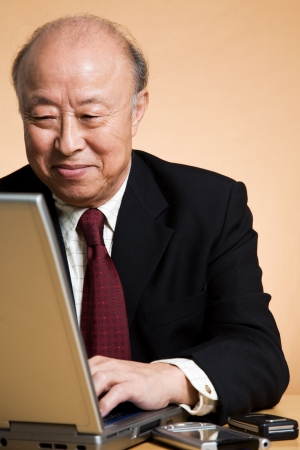 senior businessman: A shot of a senior asian businessman working on his laptop Stock Photo