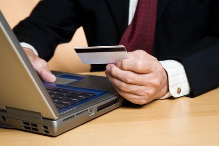 그의 노트북에서 온라인으로 쇼핑하는 사업가의 총