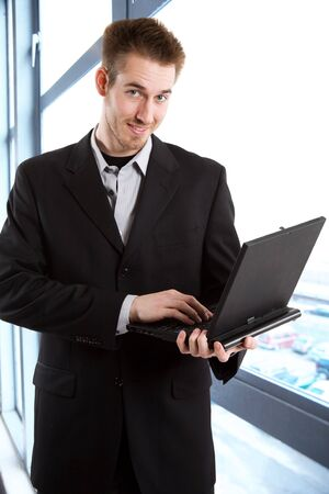 A shot of a caucasian businessman carrying a laptop in the office Stock Photo - 3112967