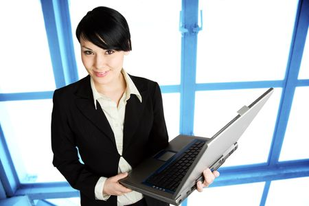 A shot of a businesswoman holding a laptop working in the office