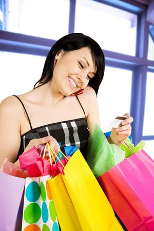 A shot of woman holding shopping bags and calling her credit card bank photo