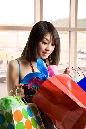 A shot of a beautiful asian woman looking at her shopping bags Stock Photo - 3177713
