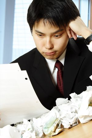 A shot of a stressed asian businessman working hard in the office with paper all over the table Stock Photo - 3205655