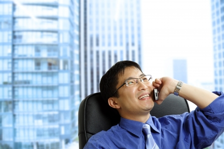 A shot of an asian businessman talking on the phone at the office photo