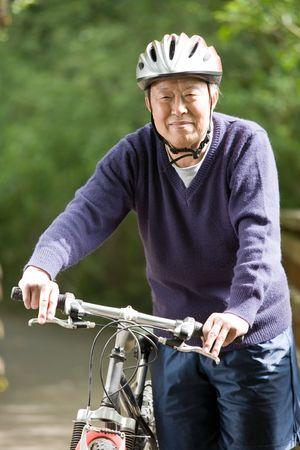 A shot of a mature asian man riding a bike