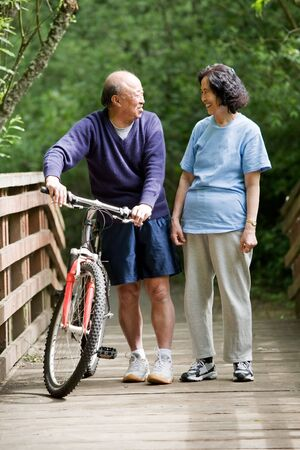 A shot of a couple asian mature talking while walking and exercising at a park
