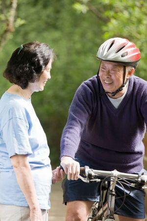 운동하는 동안 야외 이야기하는 성숙한 아시아의 커플의 쐈 어.