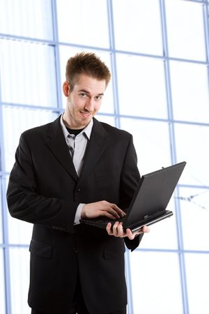A shot of a caucasian businessman carrying a laptop working in an office Stock Photo - 3234202