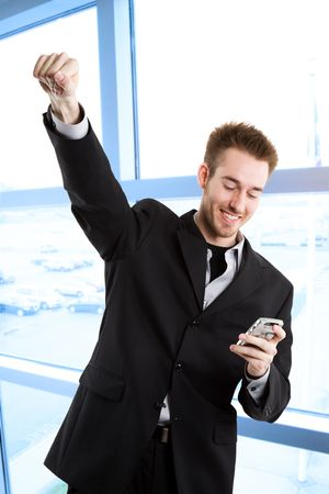 A shot of a happy caucasian businessman raising his arms in happiness after receiving a text message Stock Photo - 3234203