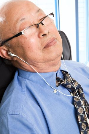 A shot of a senior asian businessman relaxing and listening to music in the office